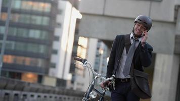 empresário falando no celular sentado em sua bicicleta na cidade video