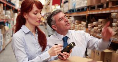 gerente de armazém e chefe usando um dispositivo touchscreen