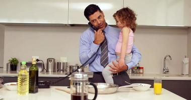 padre sorridente che tiene la sua giovane figlia parlando al telefono