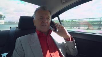 chefe idoso conversa por telefone com parceiro de negócios a caminho do trabalho