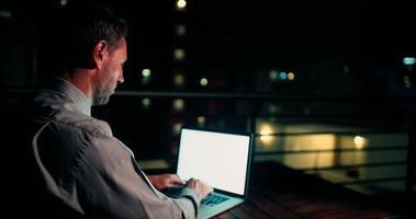 reifer Mann, der auf Balkon sitzt und am Laptop arbeitet