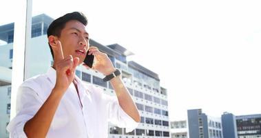 Ein Mann ruft auf seinem Smartphone an und zeigt auf etwas