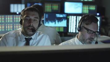 Two stockbrokers are talking on a headset while working on a computer in a dark office filled with display screens.