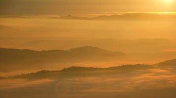 amanecer de un panorama montañoso sobre la ciudad con una densa capa de niebla