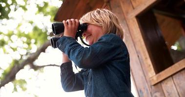 menino sentado em uma casa da árvore olhando através de binóculos video
