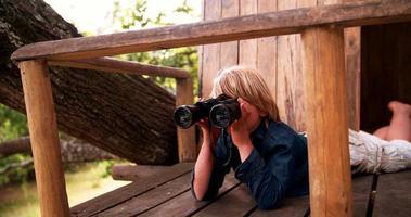 menino deitado em uma casa da árvore olhando através de binóculos video