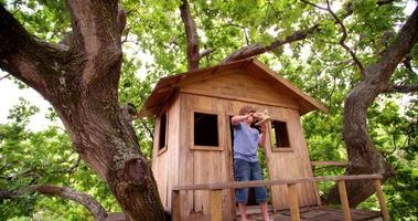 menino em uma casa na árvore brincando com um avião de brinquedo de madeira