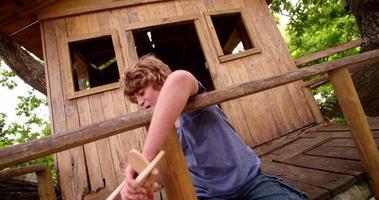 menino sentado em uma casa na árvore brincando com um avião de madeira de brinquedo