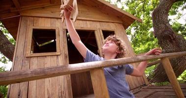 menino brincando com um avião de brinquedo de madeira na casa da árvore