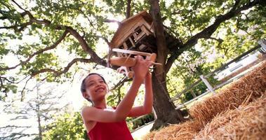 menina brincando debaixo de uma árvore com um avião de madeira de brinquedo