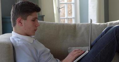 Adolescente sentado en el sofá usando la computadora portátil en casa rodada en r3d