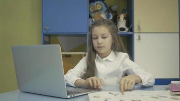 Young girl Using a Laptop and Doing Homework in School video