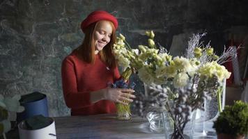 fille de fleuriste faisant une composition de fleurs