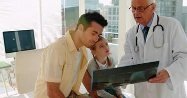 Doctor showing x-ray report to male patient video