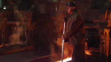 Porträt eines Arbeiters der Schwerindustrie, der die Qualitätskontrolle in der Gießerei durchführt. raues industrielles Umfeld. Weitwinkelaufnahme.