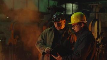 Ingenieur und Arbeiter unterhalten sich in der Gießerei. Ingenieur mit Tablet. raues industrielles Umfeld.