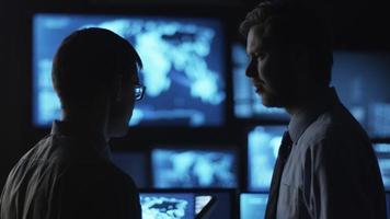 dois funcionários do sexo masculino estão conversando em uma sala de monitoramento escura, cheia de telas de exibição.