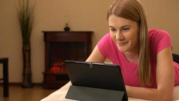 Hermosa mujer joven y atractiva en una camiseta rosa comunicándose con amigos a través de un mensajero video
