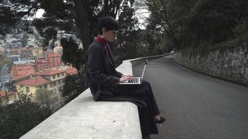 junge Geschäftsfrau, die draußen am Computer arbeitet