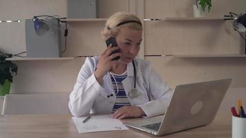 Therapist talking on the mobile phone on her desk computer and prescription video