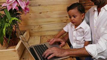 padre che insegna a suo figlio sul laptop