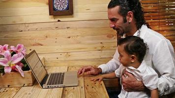 père enseignant son fils sur ordinateur portable