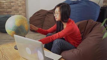 Frau mit langen schwarzen Haaren drehen den Globus Land wählen