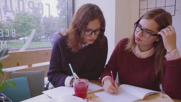 Les étudiantes étudient dans le café deux amies apprenant ensemble