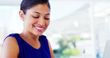 mulher sorrindo e usando laptop