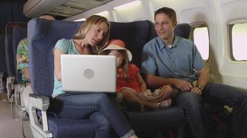 Familie mit Laptop im Flugzeug