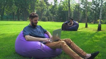 ein junger Mann im blauen Hemd, der in einem Stuhl Ottoman Park sitzt und am Computer arbeitet