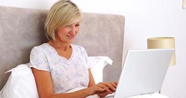 donna felice utilizzando laptop a letto