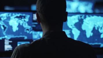 un impiegato maschio controlla mappe e dati sugli schermi del computer in una stanza buia dell'ufficio.