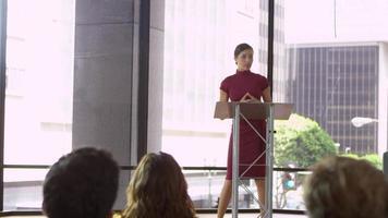 mujer joven en un atril presentando un seminario de negocios, filmado en r3d