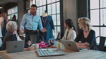 quatro designers de moda em reunião discutindo roupas