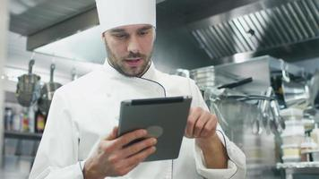 Professional chef in a commercial kitchen in a restaurant or hotel is using a tablet computer.