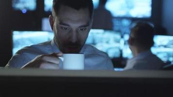 Happy technical support specialist is drinking coffee while working on a computer in a dark monitoring room filled with display screens.