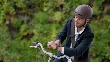 homem andando de bicicleta na rua da cidade usando tablet e relógio inteligente video