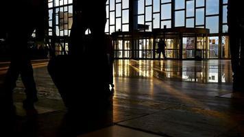 Siluetas de personas caminando con equipaje en un aeropuerto internacional video