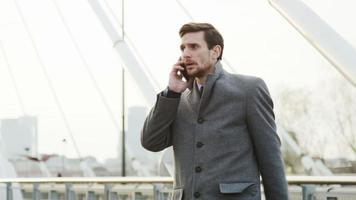 junger Geschäftsmann, der draußen und wütend ist, während er am Telefon spricht video