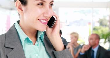 imprenditrice con telefonata con i suoi colleghi dietro