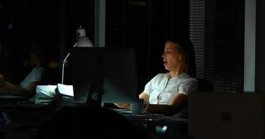 Boss giving new work to businesswoman at night