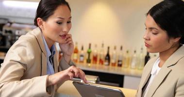 Geschäftsfrauen, die Tablette betrachten und am Telefon sprechen