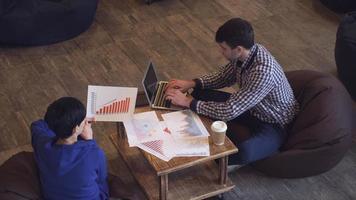 Eine Frau hält den Wachstumsplan, ein Mann tippt auf einem Laptop