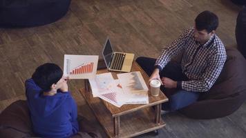 Eine Frau hält eine Grafik, ein Mann trinkt einen Schluck Kaffee und tippt auf der Tastatur