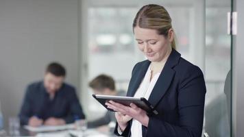 femme d & # 39; affaires utilise une tablette pendant que la réunion d & # 39; affaires s'exécute en arrière-plan video