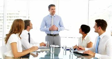 empresário recebendo elogios de seus funcionários em reunião