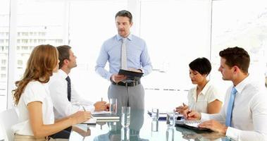 empresário em pé e falando durante a reunião