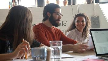 diseñadores sentados a la mesa con reunión creativa video
