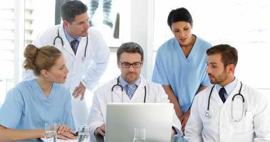 Arzt plaudert mit seinen Mitarbeitern während eines Treffens